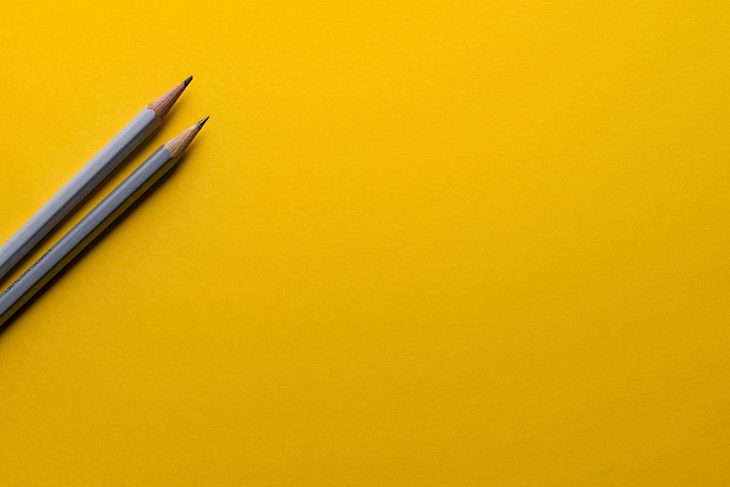 Yellow background with two gray pencil