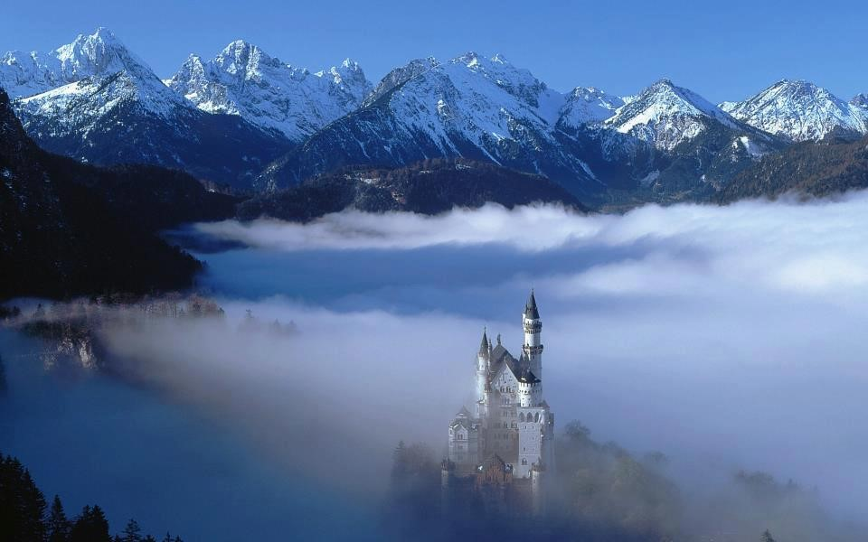 """Photo of the """"fairytale castle"""" of Neuschwanstein, a turreted castle with snow covered mountains in the background"""